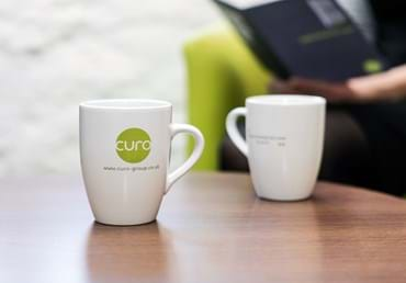 Curo coffee cup and customer reading.jpg