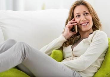 Lady using phone sat on phone - istockphoto.jpg